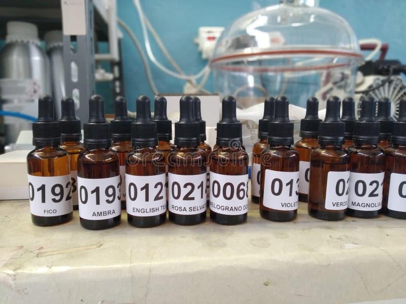 Botellas de la esencia del perfume pequeñas y campana marrones del vacío fotos de archivo