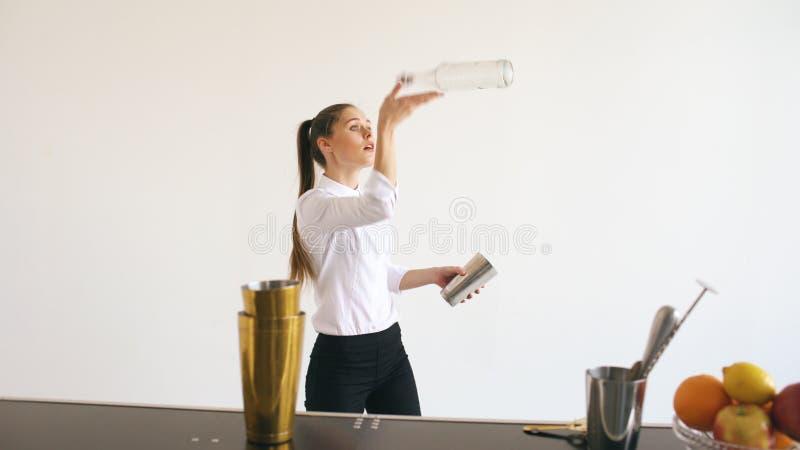 Botellas de la muchacha del camarero de Professinal y cóctel de la sacudida que hacen juegos malabares en la tabla móvil de la ba fotos de archivo