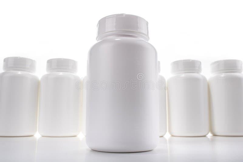 Botellas de píldora blancas en blanco alineadas en la superficie blanca con la botella ofrecida en frente fotografía de archivo