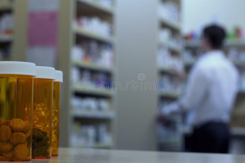 Botellas de píldora en un contador de la farmacia con el farmacéutico en fondo foto de archivo libre de regalías