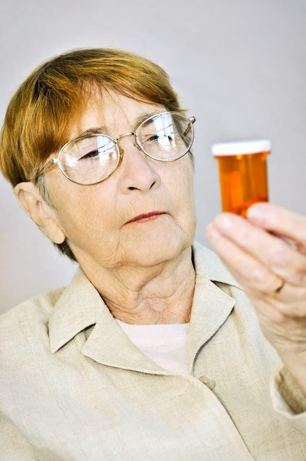 Botellas de píldora mayores de la lectura de la mujer foto de archivo libre de regalías
