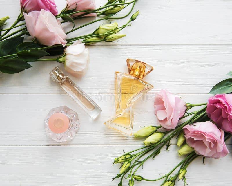 Botellas de perfume con las flores fotografía de archivo