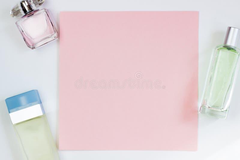 Botellas de perfume en un fondo rosado Tarjeta vac?a rosada, hoja para escribir Disposici?n para a?adir etiquetas Visi?n superior fotografía de archivo