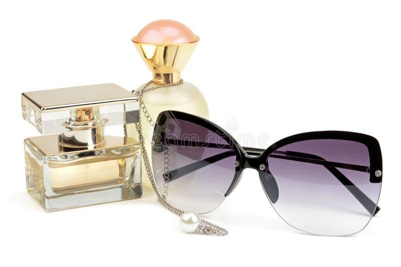 Botellas de perfume, gafas de sol y cadena fotografía de archivo libre de regalías