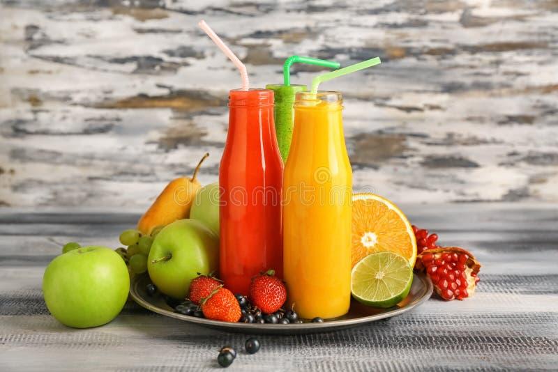 Botellas de smoothies sabrosos con las frutas en la tabla de madera imagen de archivo libre de regalías