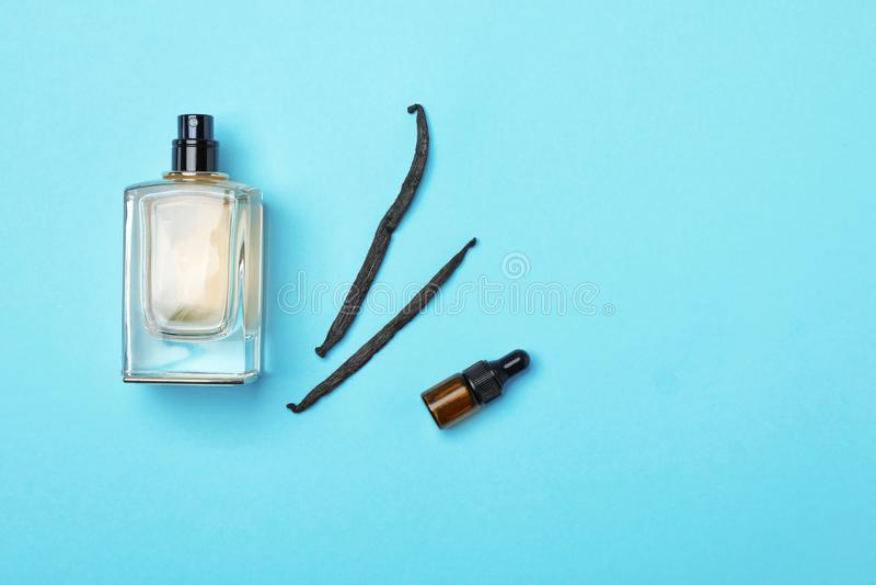 Botellas de vainas del perfume y de la vainilla en fondo del color foto de archivo libre de regalías