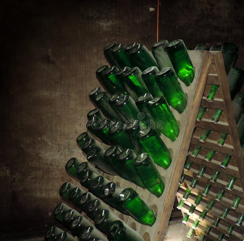 Botellas de vino antiguas que ponen en bodega Vino viejo en lagar viejo imagenes de archivo
