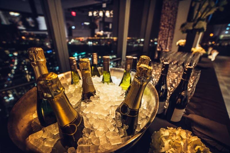 Botellas de vino de Champán en el hielo en la tabla de abastecimiento en acontecimiento de lujo de la ciudad fotografía de archivo libre de regalías