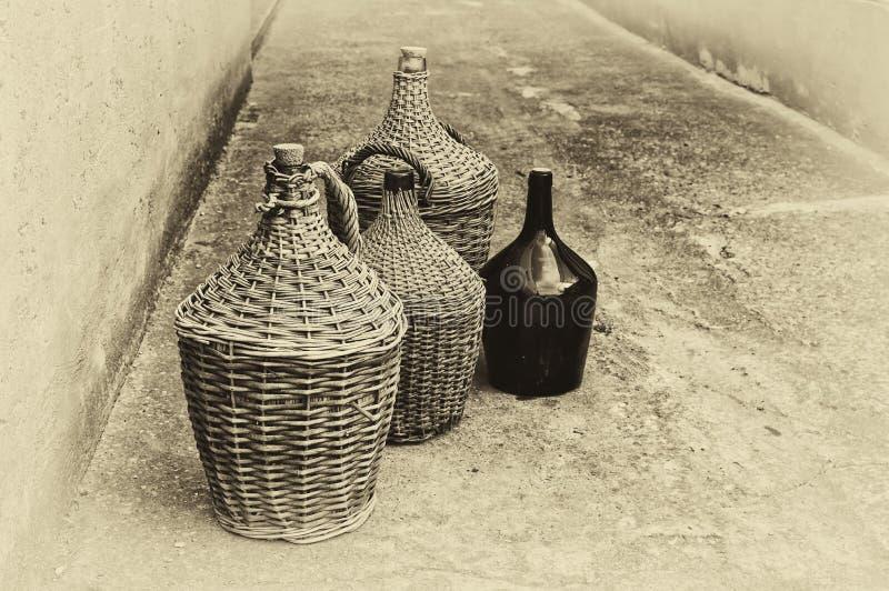 Botellas de vino de mimbre tejidas. imagenes de archivo