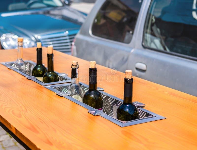 Botellas de vino que se exhiben en una fila para degustación en el fondo de los coches fotos de archivo libres de regalías