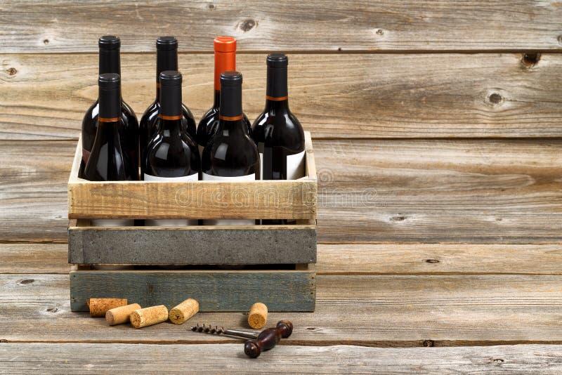 Botellas de vino rojo en cajón de madera en los tableros de madera rústicos imagen de archivo libre de regalías