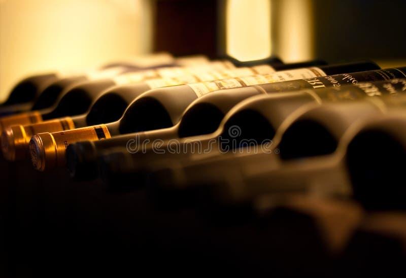 Botellas de vino rojo en un estante de madera fotografía de archivo