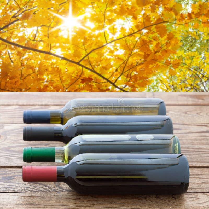 Botellas de vino tinto apiladas en la tabla de madera Fondo de la naturaleza fotos de archivo libres de regalías