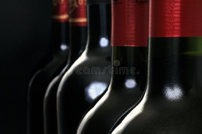 Botellas de vino tinto en primer en fondo negro imagenes de archivo