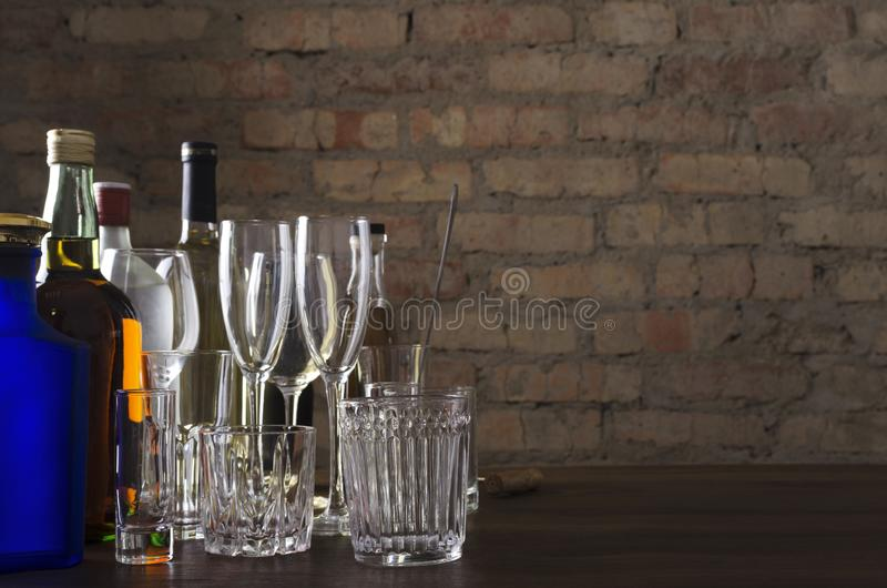 Botellas de whisky, vino y otras bebidas alcohólicas, diferentes vasos para las bebidas en la mesa contra la pared de ladrillo an fotos de archivo