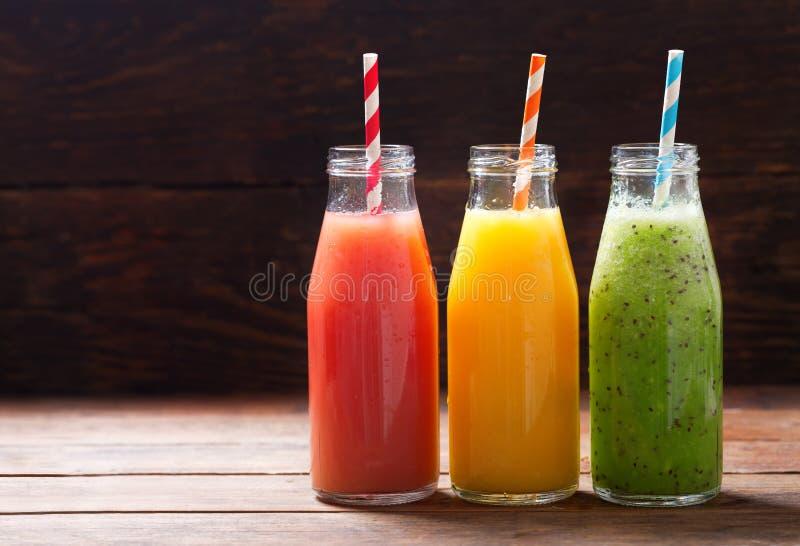 Botellas de zumo de fruta fresca y de smoothie imagen de archivo