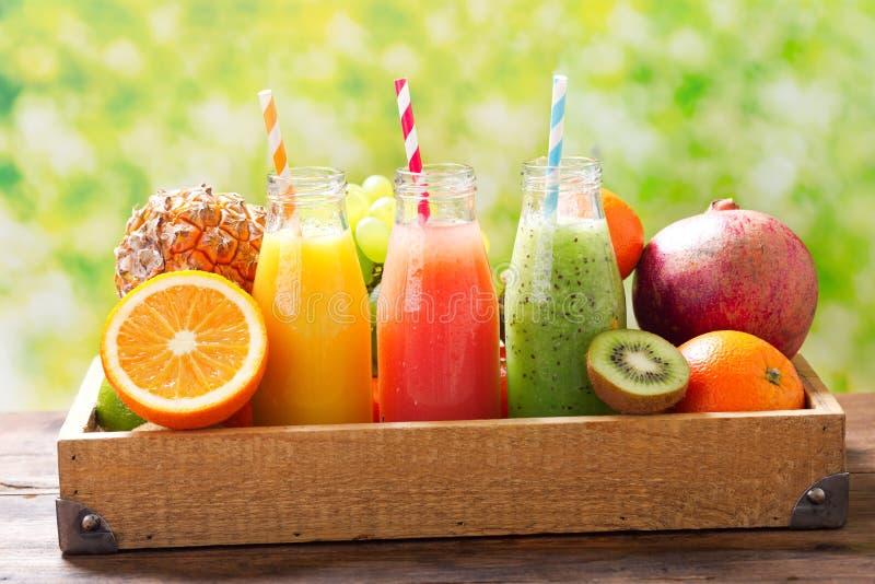 Botellas de zumo de fruta y de smoothie con las frutas frescas foto de archivo