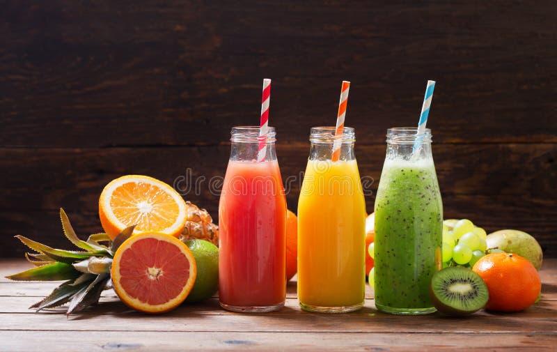 Botellas de zumo de fruta y de smoothie con las frutas frescas imagen de archivo libre de regalías