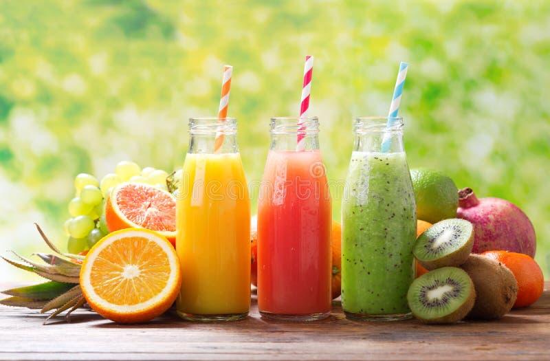 Botellas de zumo de fruta y de smoothie con las frutas frescas fotografía de archivo
