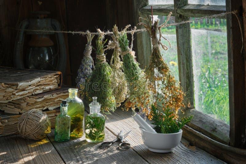 Botellas del tinte o de la infusión, libros viejos, mortero y manojos colgantes de hierbas medicinales secas fotografía de archivo