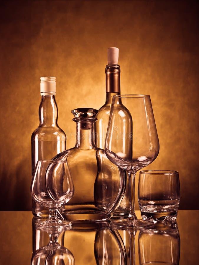 Botellas del whisky, del coñac y de vino con los vidrios imagenes de archivo