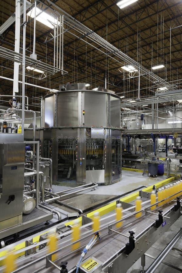 Botellas en cadena de producción en la planta de embotellamiento imágenes de archivo libres de regalías