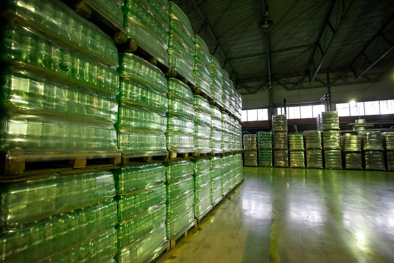 Botellas envueltas plástico en almacén de la fábrica imagenes de archivo