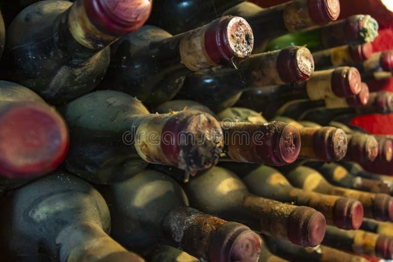 Botellas muy viejas y polvorientas apiladas en almacén Pila de botellas de vino polvorientas muy viejas foto de archivo libre de regalías