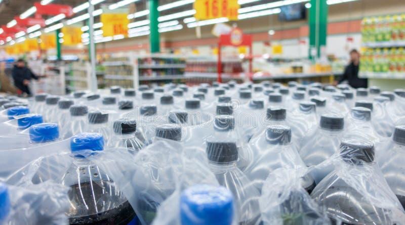 Botellas plásticas en paquetes Botellas de agua - fondo plástico de la comida de la tienda del almacén de la fábrica de las botel fotos de archivo