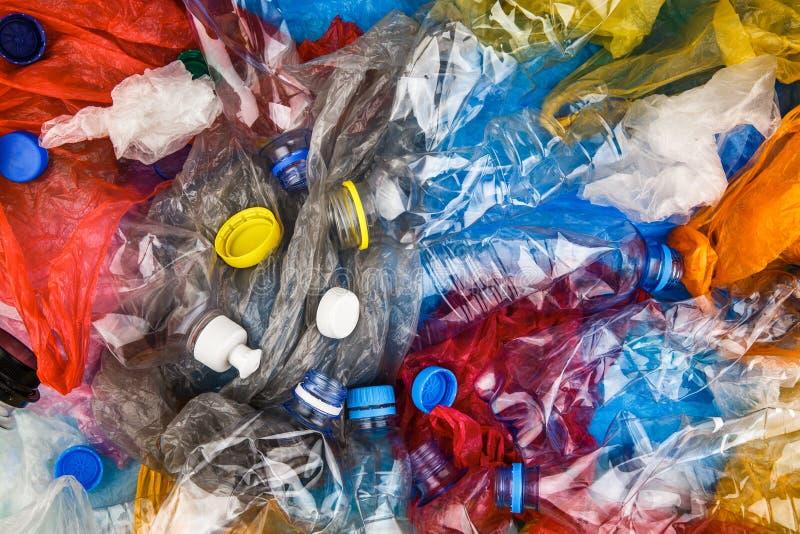 Botellas plásticas multicoloras, casquillos, basura sucia de los bolsos foto de archivo libre de regalías