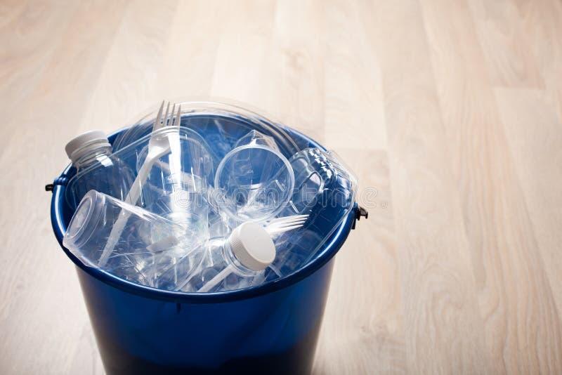 Botellas plásticas reciclables limpias, envases, tazas en compartimiento de basura reutilización plástica de la gestión de desech imagenes de archivo