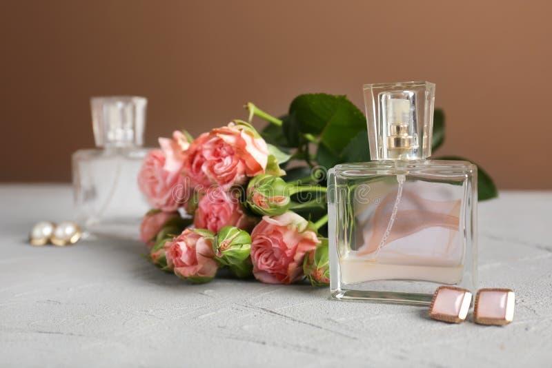 Botellas transparentes de perfume con las flores y los pendientes hermosos en la tabla gris foto de archivo