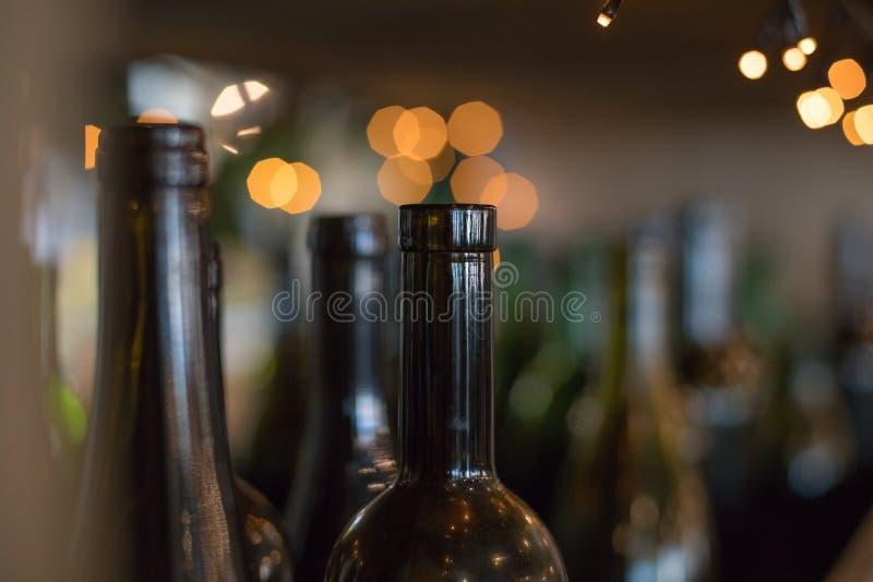 Botellas vacías de cristal elemento-oscuras interiores decorativas en fondo brillante Muchas botellas de vino de cristal como dec fotos de archivo