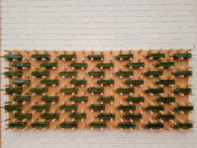 Botellas verdes en el tablero de madera y el fondo blanco de la pared de ladrillo imagen de archivo libre de regalías