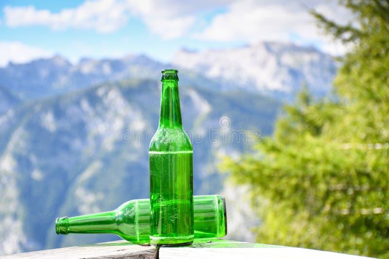 Botellas verdes vacías de cerveza en una cerca de madera imágenes de archivo libres de regalías