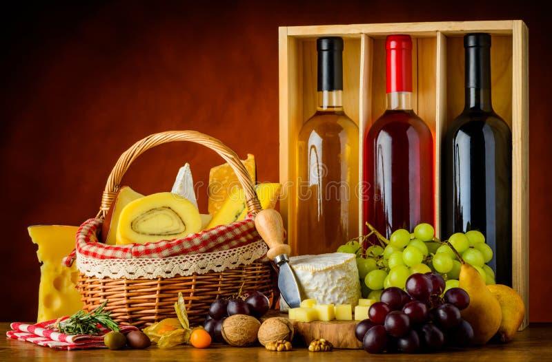 Botellas vino, comida y queso imagen de archivo