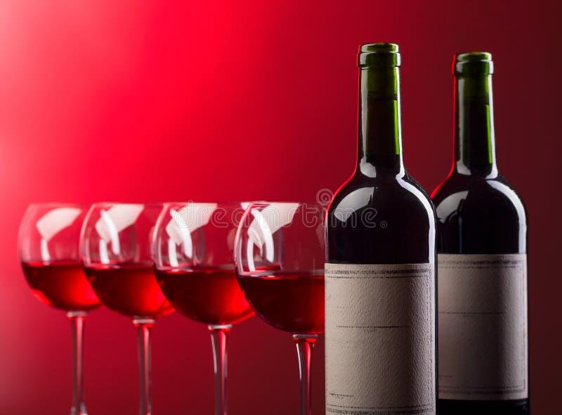 Botellas y vidrios de vino rosado en un fondo oscuro fotografía de archivo libre de regalías