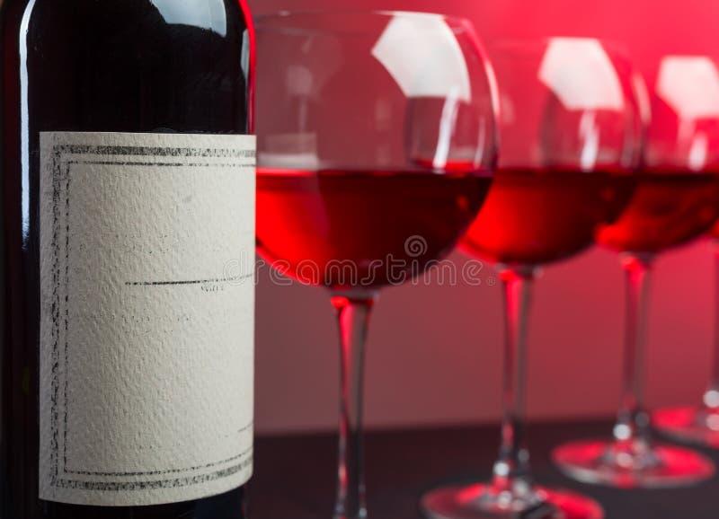 Botellas y vidrios de vino rosado en un fondo oscuro imágenes de archivo libres de regalías
