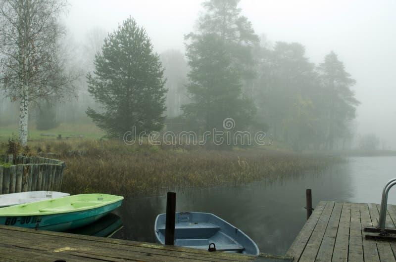 Boten in de mist dichtbij de kust stock foto
