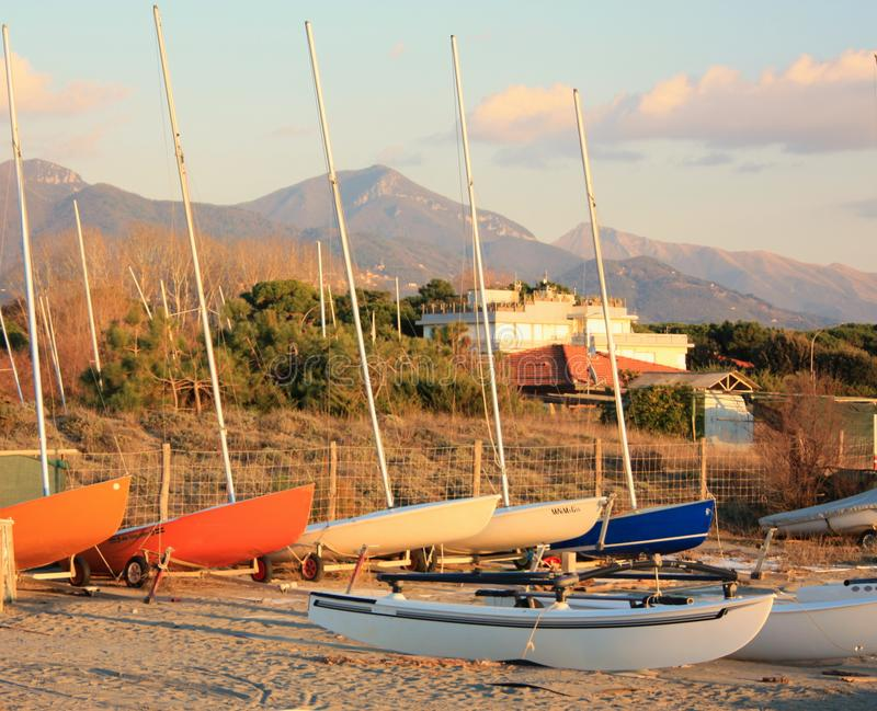 Boten die op het strand op hun parkeerterrein rusten die op de zomer wachten stock foto's