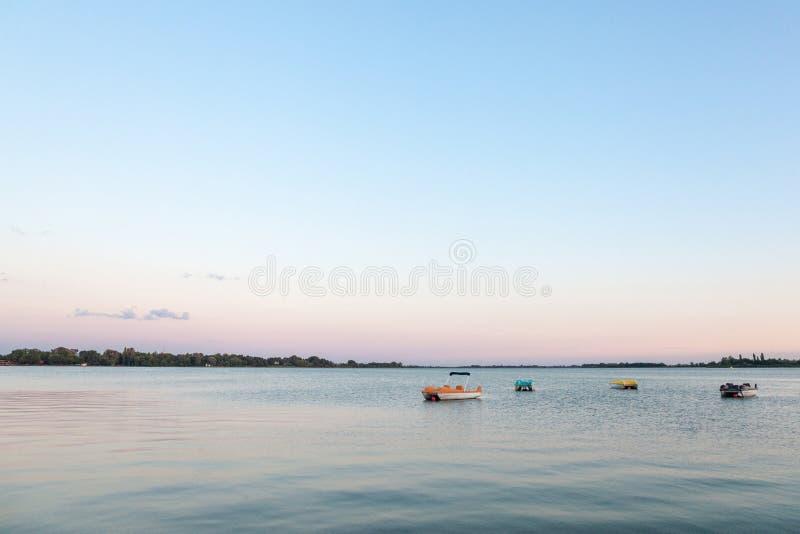 Boten en pedalos die op de blauwe die wateren van Palic-Meer, in Subotica, Servië, tijdens een de zomerzonsondergang ook rusten a stock foto's