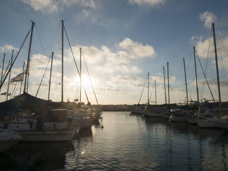 Boten in jaffahaven, Israëlische vlag die op de wind golven Bewolkte hemel stock foto's