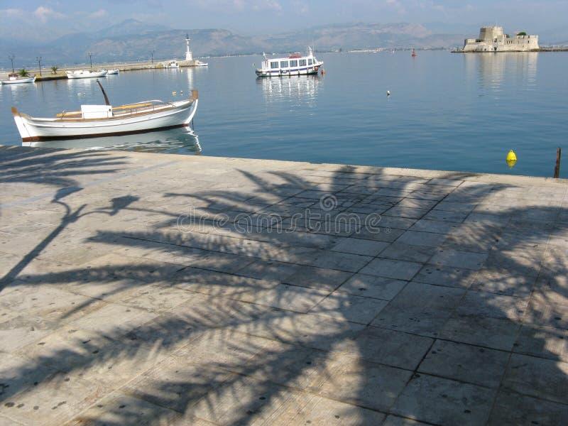 Boten in mediterrane haven en palmschaduw, NAFPLIO, GRIEKENLAND stock fotografie
