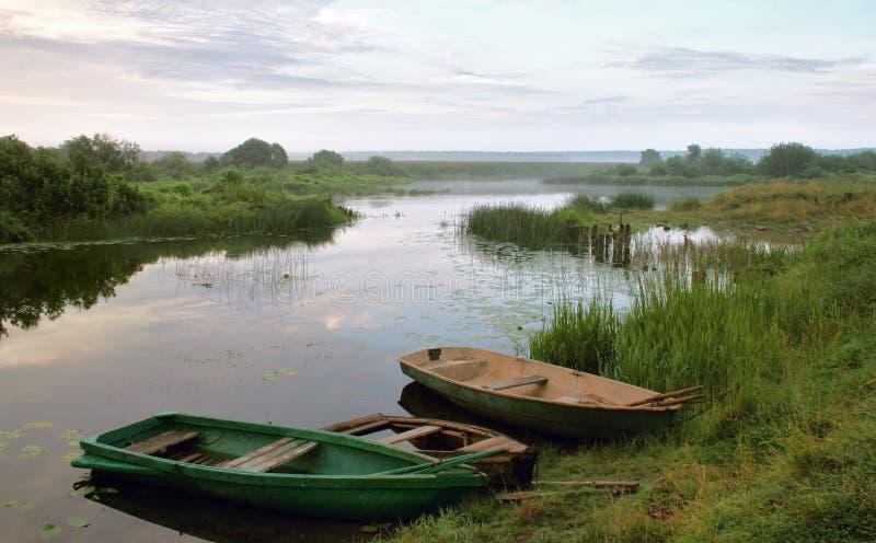 Boten naast rivieroever matutinal landschap royalty-vrije stock foto