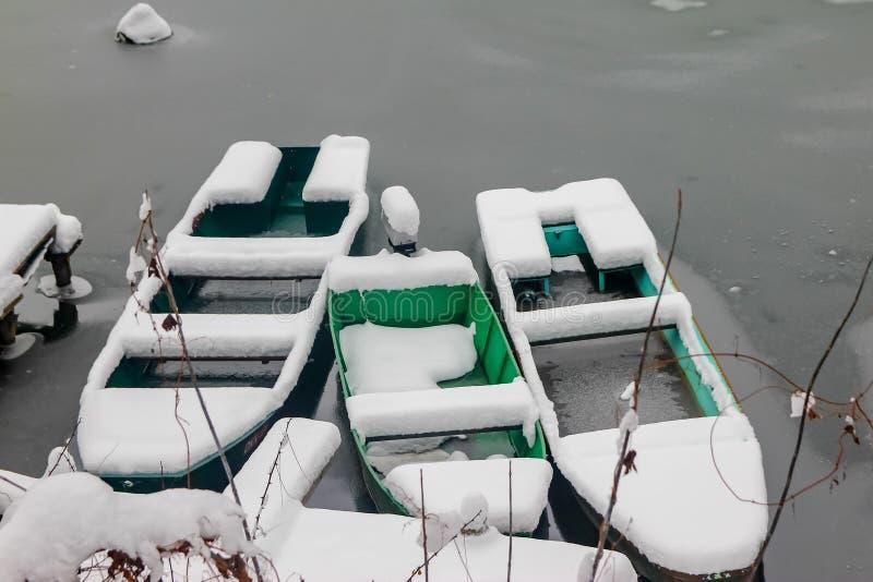Boten op de bevroren die rivier met sneeuw wordt behandeld royalty-vrije stock afbeeldingen