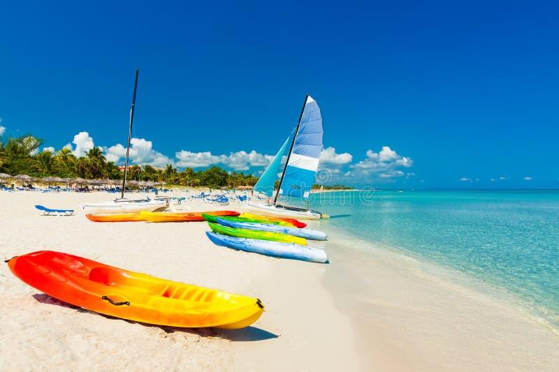 Boten op een tropisch strand in Cuba stock afbeeldingen