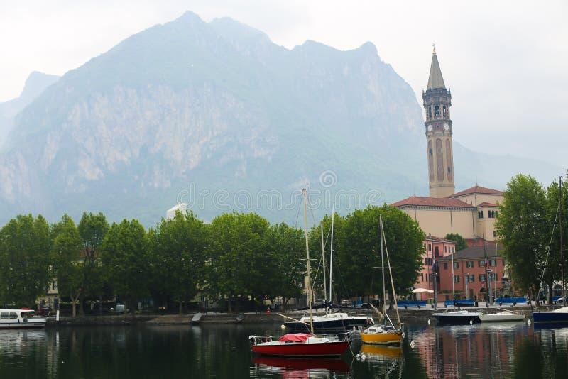 Boten op meer Como dichtbij kerk met toren, bomen en berg op achtergrond stock afbeelding