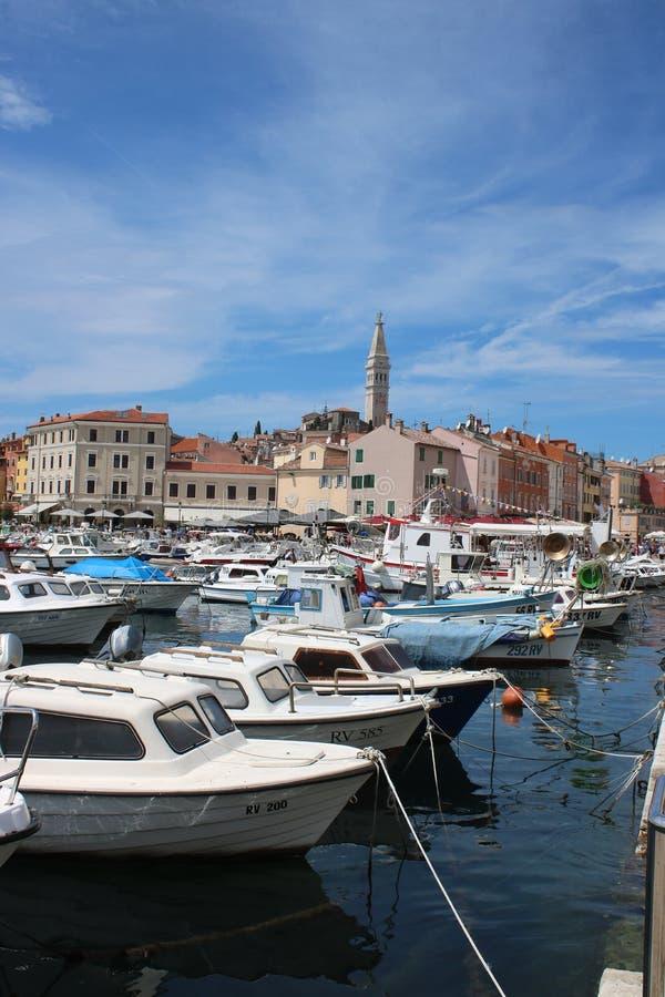 Boten in Rovinj-haven, Kroatië met erachter stad stock foto