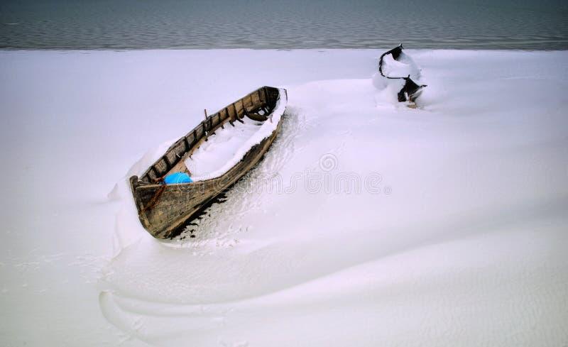 Boten in sneeuw op een meerkust royalty-vrije stock fotografie