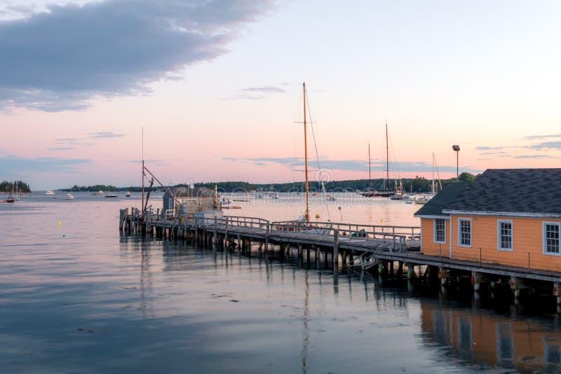 Botenhuis en dok in de haven bij schemer stock afbeelding